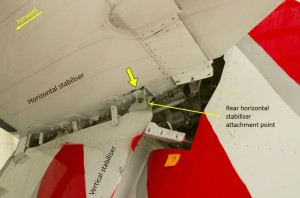 Horizontal-to-vertical stabiliser attachment with the aerodynamic fairings removed. View looking upwards at the underside of the horizontal stabiliser. The thick yellow arrow indicates cracking in the composite structure around the rear attachment point (Credit: ATSB)