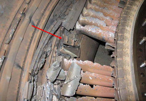 View from the rear of the location of the missing 3rd stage vane cluster with an arrow pointing to the piece of 3rd stage vane cluster inner shroud (Credit: P&W via NTSB)
