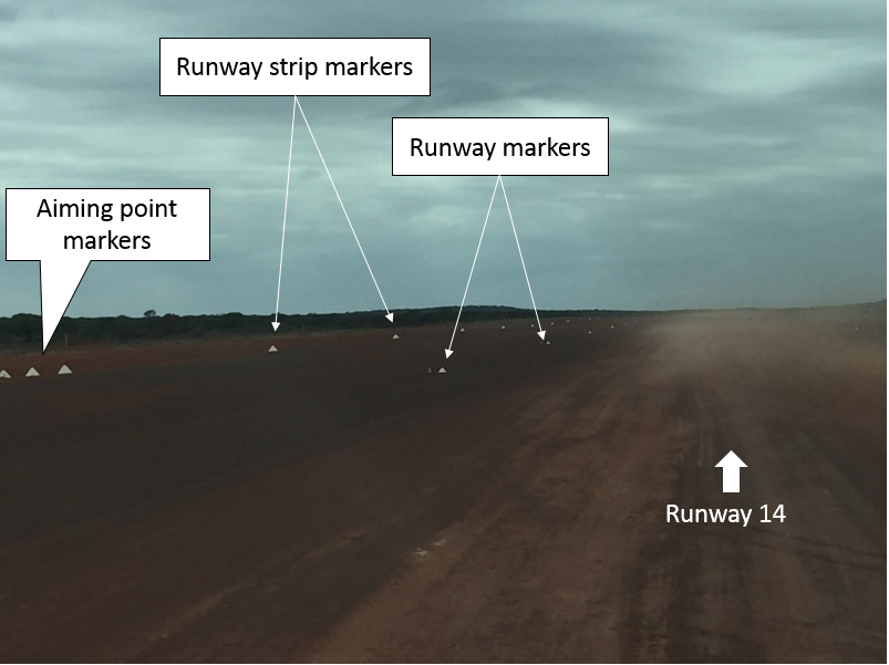 Darlot Airport runway 14 and left side of runway strip as viewed from the right seat of the aircraft with white frangible cones used as markers. Raised dust extends from the centre of the runway across the southern side of the runway strip. (Credit: ATSB/Pilot)