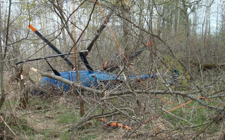 Wreckage of Rotor Blade MD Helicopters 369E N629JK on its side in trees (Credit: NTSB)