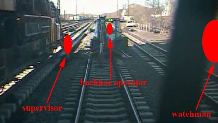 The view from the train's forward camera, approximately 0.5s before impact at over 100mph, with workers redacted by red symbols (Credit: NTSB)