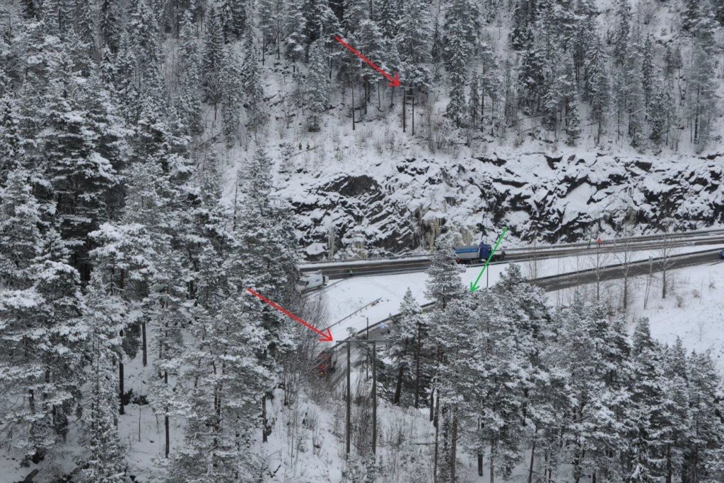 Accident Site Norsk Luftambulanse Airbus Helicopters EC135P2+ LN-OOI. Photo taken facing east on the same day as the accident. The power line poles are marked with red arrows. The  helicopter wreckage is located behind the trees marked with a green arrow. (Credit: Police via AIBN)