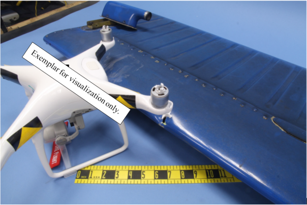 """""""Angled view comparing common drone to impact marks. The drone in the photo is an exemplar of a popular drone used to illustrate size comparison. Numerous manufacturers and models of drone fall into this size class. Does not necessarily depict the actual collision object """"(Credit: NTSB)"""