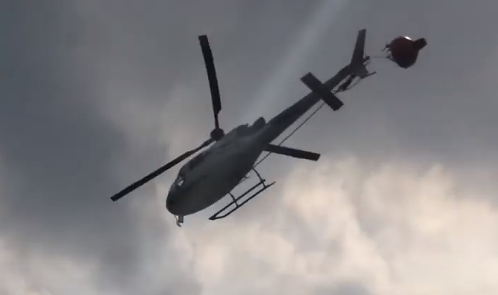 Hélilagon Airbus AS350B3e / H125 Trailing its Bambi Bucket after an Impact with its Tail Rotor while HESLO Fire-Fighting at the Piton de la Fournaise Volcano, Réunion (Credit: YouTube Video Posted by BK117)